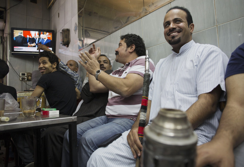 Photo - A man applauds as people gather in a tea shop to watch a state television broadcast as President Abdel-Fattah el-Sissi takes the oath of office, in the Zamalek district of Cairo, Egypt, Egypt, Sunday, June 8, 2014. El-Sissi was sworn in on Sunday as president for a four-year term, taking the reins of power in a nation roiled since 2011 by deadly unrest and economic woes. (AP Photo/Hiro Komae)