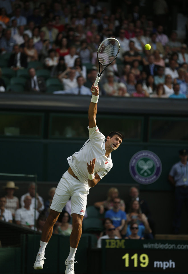 Photo - Novak Djokovic of Serbia serves to Andrey Golubev of Kazakhstan during their first round match at the All England Lawn Tennis Championships in Wimbledon, London,  Monday, June  23, 2014. (AP Photo/Pavel Golovkin)