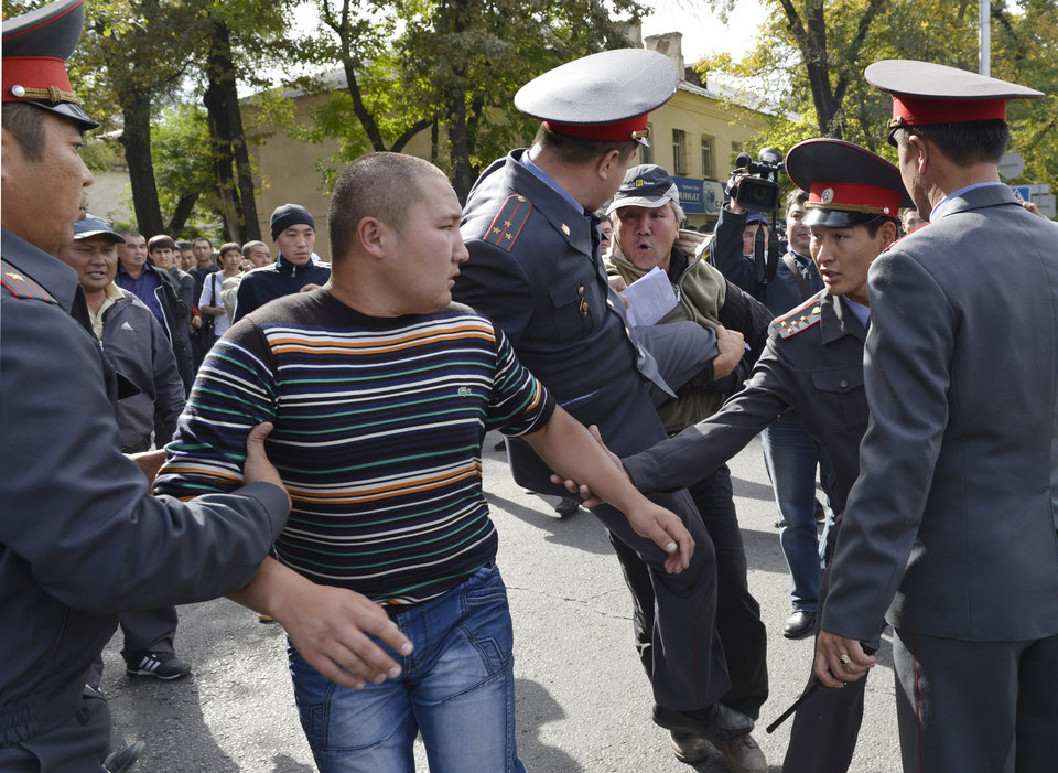Police officers detain protesters in downtown Bishkek, Kyrgyz capital on Wednesday, Oct. 3, 2012. Around 1,000 people gathered in the center of the city for a rally, organized by nationalist politicians Sapar Zhaparov and Kamchibek Tashiyev, ostensibly to demand the nationalization of a controversial gold mine in the east of the Central Asian nation. Police officers protecting the government building, known as the White House, used dogs and smoke bombs to disperse a group of young men who attempted to scale the gates. (AP Photo/ Vladimir Voronin)