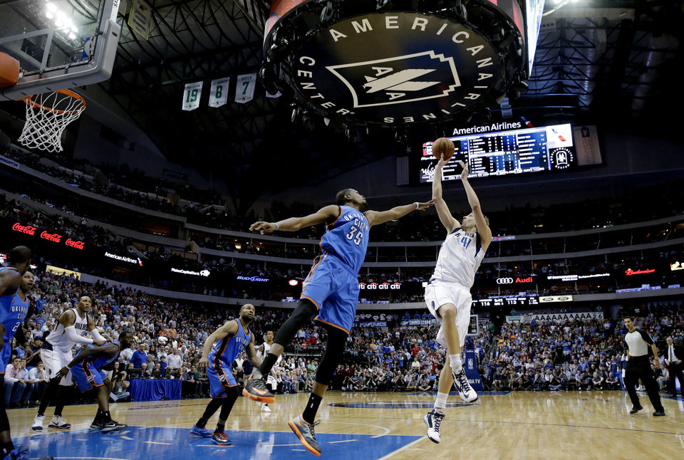 Dallas Mavericks forward Dirk Nowitzki (41)shoots against Oklahoma City Thunder forward Kevin Durant (35) during overtime of an NBA basketball game Tuesday, March 25, 2014, in Dallas. The Mavericks won 128-119. (AP Photo/LM Otero)
