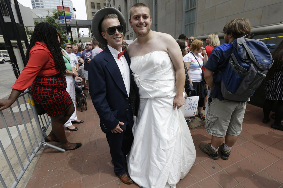 Photo - Matt Morris, left, and Jon Bradford pose outside the Potter Stewart United States Courthouse, Wednesday, Aug. 6, 2014, in Cincinnati. The couple hope to marry. Three judges of the 6th U.S. Circuit Court of Appeals in Cincinnati are set to hear arguments Wednesday in six gay marriage fights from four states, Kentucky, Michigan, Ohio and Tennessee. (AP Photo/Al Behrman)