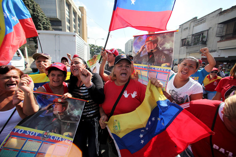 Supporters of Venezuela's President Hugo Chavez celebrate his return, outside the Carlos Arvelo Military Hospital in Caracas, Venezuela, Monday, Feb. 18, 2013. Chavez returned to Venezuela early Monday after more than two months of medical treatment in Cuba following cancer surgery. Vice President Nicolas Maduro said on television that Chavez arrived at 2:30 a.m. and was taken to the military hospital in Caracas, where he will continue his treatment. (AP Photo/Fernando Llano)