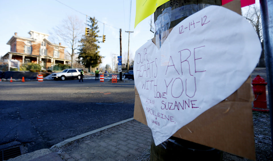 Photo - A sign on a post shows support for the victims of a gunman who opened fire inside Sandy Hook Elementary School a day earlier as police officers stand at a road block, Saturday, Dec. 15, 2012, in Sandy Hook village of Newtown, Conn. The massacre of 26 children and adults at Sandy Hook Elementary school elicited horror and soul-searching around the world even as it raised more basic questions about why the gunman, 20-year-old Adam Lanza, would have been driven to such a crime and how he chose his victims.  (AP Photo/Julio Cortez)