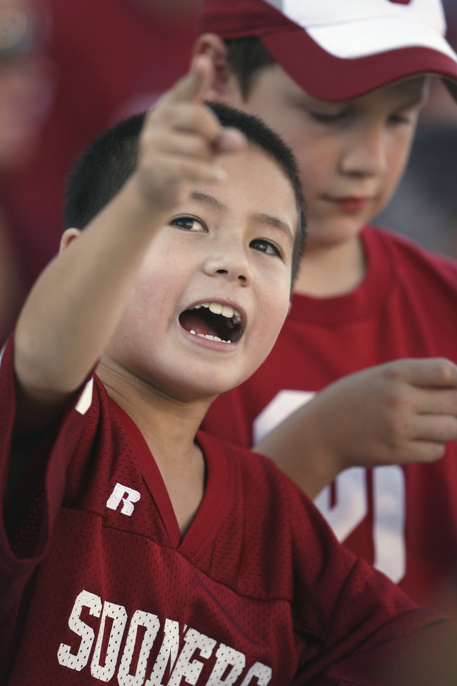 Photo - Ethan Bui, 8, of Edmond watched the college football game between the University of Oklahoma Sooners (OU) and Utah State University Aggies (USU) at the Gaylord Family-Oklahoma Memorial Stadium on Saturday, Sept. 4, 2010, in Norman, Okla.   Photo by Steve Sisney, The Oklahoman