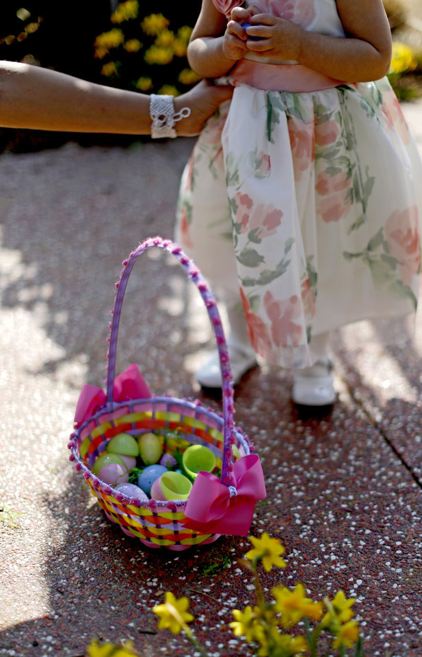 Photo - A basket full of eggs rests at the feet of 17-month-old Victoria Saldivar from Oklahoma City during the Myriad Gardens Annual Easter Egg Hunt in downtown Oklahoma City, Saturday, March 30, 2013. Photo by Bryan Terry, The Oklahoman