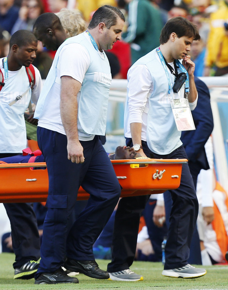 Photo - Netherlands' Bruno Martins Indi is carried off the pitch in a stretcher after a collision with Australia's Tim Cahill during the group B World Cup soccer match between Australia and the Netherlands at the Estadio Beira-Rio in Porto Alegre, Brazil, Wednesday, June 18, 2014.  (AP Photo/Jon Super)