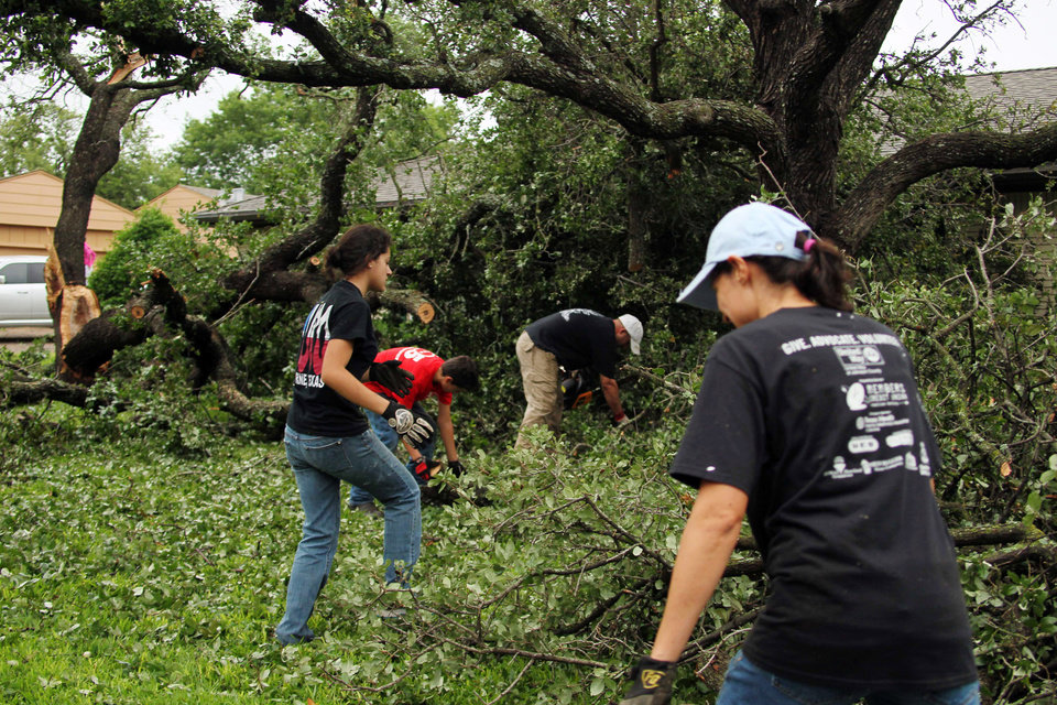 Photo - From left, the Keith family, Jordan, Alex, Josh and Connie clean a lot damaged by Wednesday's tornado in Cleburne, Texas on Thursday, May 16, 2013. Ten tornadoes touched down in several small communities in Texas overnight, leaving at least six people dead, dozens injured and hundreds homeless. Emergency responders were still searching for missing people Thursday afternoon. (AP Photo/Ron Russek II)
