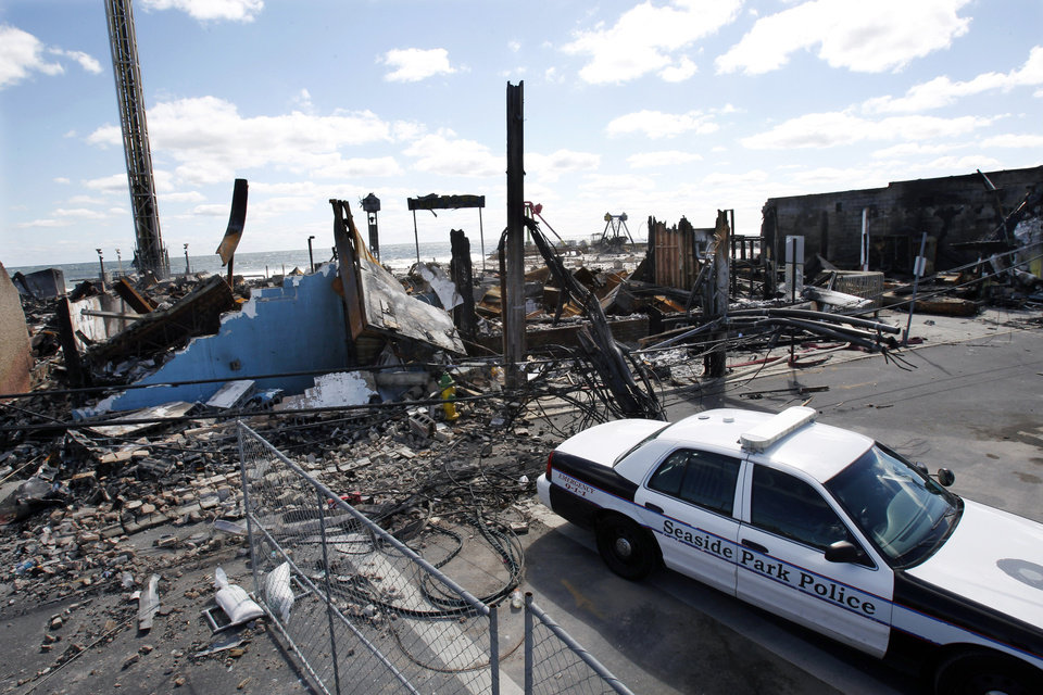 Photo - A Seaside Park police officer sits in his cruiser near the charred rubble in Seaside Park, N.J., Tuesday, Sept. 17, 2013, after a fire last Thursday that started near a frozen custard stand in Seaside Park,  quickly spread north into neighboring Seaside Heights. More than 50 businesses in the two towns were destroyed. The massive boardwalk fire in New Jersey began accidentally, the result of an electrical problem, an official briefed on the investigation said Tuesday. (AP Photo/Mel Evans)