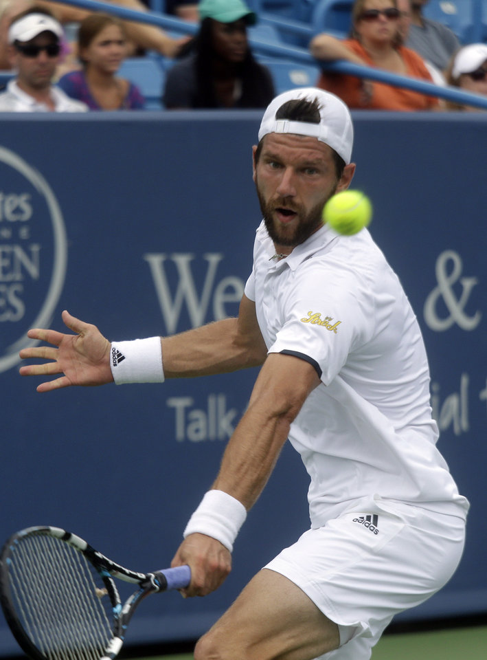 Photo - Jurgen Melzer, from Austria, hits a backhand during a first-round match against Lleyton Hewitt, from Australia, at the Western & Southern Open tennis tournament, Sunday, Aug. 10, 2014, in Mason, Ohio. (AP Photo/Al Behrman)