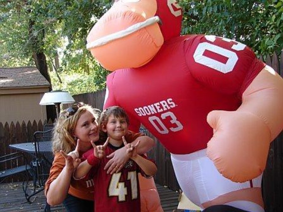 "My little friend Myles is a Sooner fan all the way! He was just being nice when he made the ""Hook 'Em"" sign with me during ""the big game"" because he didn't want me to feel left out...  :-) I joke with his Dad that I hope he can forgive his son...it's a long running joke---we have a great time!  Little boy- Myles Stehr    Texas fan- Victoria Jimenez  and third ""person""...blow-up Sooner guy    ;-)<br/><b>Community Photo By:</b> Robert Martin<br/><b>Submitted By:</b> Victoria, Harrah"