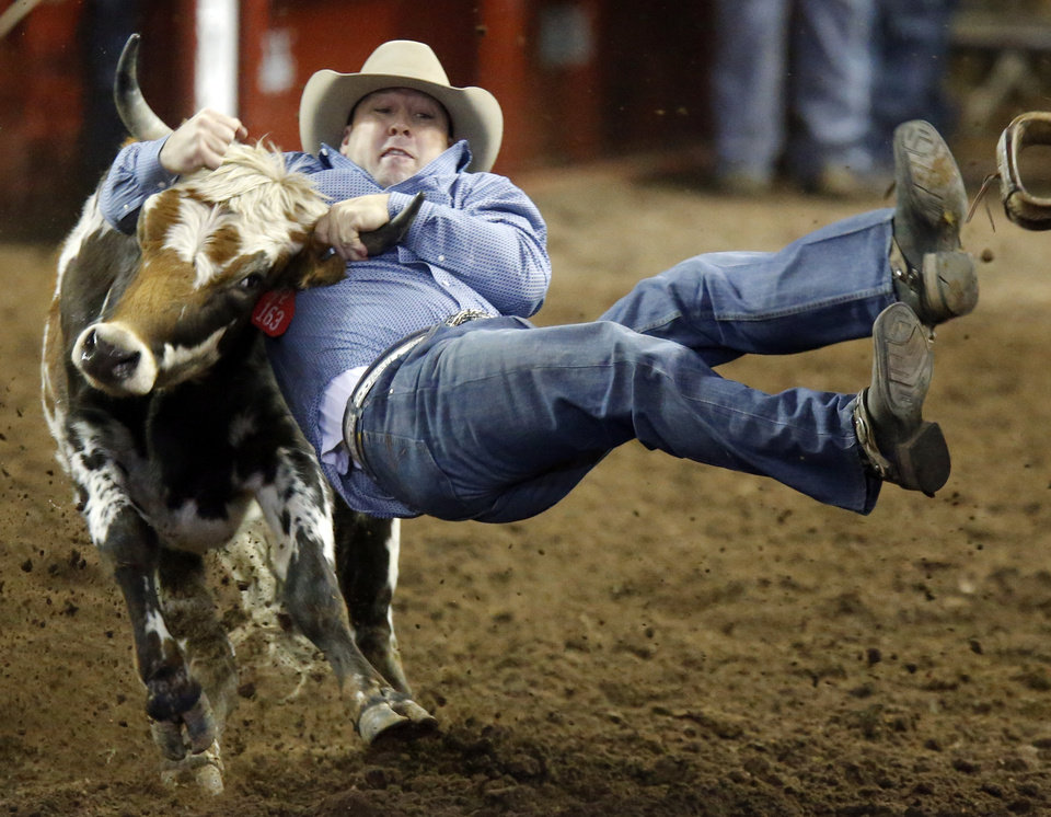 Brian Barefoot flies through the air during the steer wrestling event at the International Finals Rodeo at the State Fair Arena in Oklahoma City,  Saturday,Jan. 19, 2013. Photo by Sarah Phipps, The Oklahoman