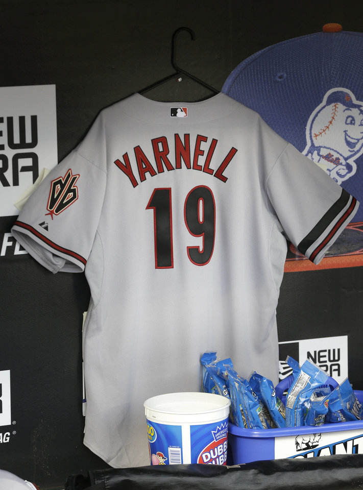 Photo - A jersey honoring the 19 firefighters who died in the wildfire in Yarnell, Ariz., hangs in the Arizona Diamondback's dugout before the baseball game against the New York Mets at Citi Field, Monday, July 1, 2013 in New York. The firefighters died Sunday. (AP Photo/Seth Wenig)