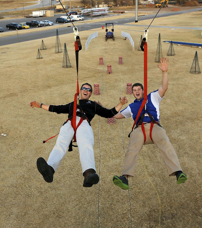Andrew Barry, left, and Jake Lang begin their ride Friday on the SandRidge Santa Zip line. Construction projects and improvements have begun in Oklahoma City's Boathouse District, including the portable zip line.  Photo by Jim Beckel, The Oklahoman