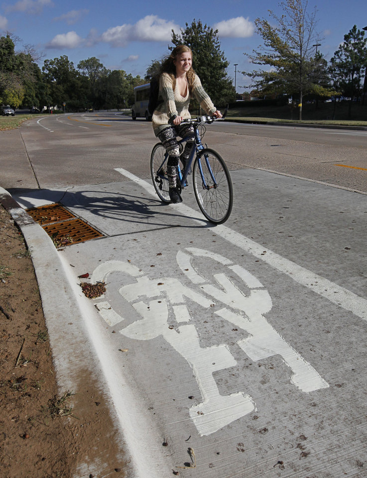 Photo - University of Central Oklahoma student Molly Reaves heads to class on Edmond's first bike lane along University Drive, which opened on Sunday. PHOTO BY PAUL HELLSTERN, THE OKLAHOMAN.  PAUL HELLSTERN - THE OKLAHOMAN
