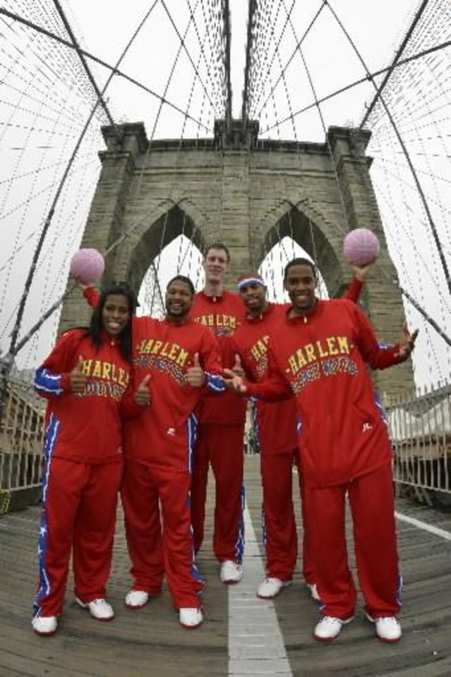 From left TNT Maddox, Handles Franklin, Paul 'Tiny' Sturgess, Hammer Harrison and Cheese Chisholm of the Harlem Globetrotters pose for photos while dribbling across the Brooklyn Bridge using PINK basketballs to show their support for National Breast Cancer Awareness on Wednesday Oct. 3, 2012, in New York. (AP)