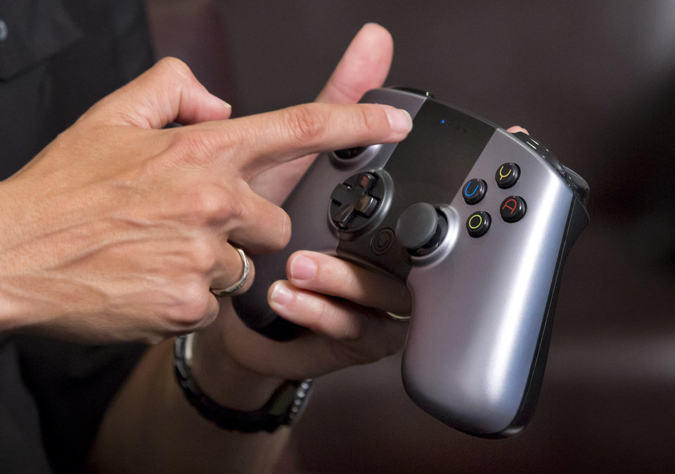 Photo - Julie Uhrman, chief executive of Android game console maker Ouya, describes the controller of the new console, during an an interview in New York, Tuesday, June 25, 2013.  Ouya, that went on sale Tuesday for $99, aims to challenge the dominance of the Xboxes, Nintendos and PlayStations of the world. The launch follows a successful funding campaign through the group-fundraising site Kickstarter, but it's unclear whether the console will enjoy broader success. (AP Photo/Richard Drew) ORG XMIT: NYRD104
