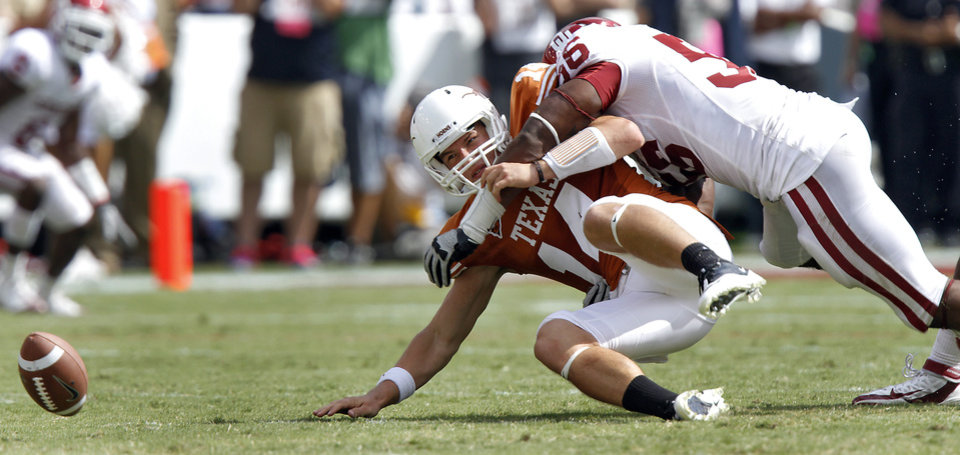 Photo - Oklahoma's Ronnell Lewis (56) forces a fumble on Texas quarterback David Ash (14) during the Red River Rivalry college football game between the University of Oklahoma Sooners (OU) and the University of Texas Longhorns (UT) at the Cotton Bowl in Dallas, Saturday, Oct. 8, 2011. Photo by Chris Landsberger, The Oklahoman