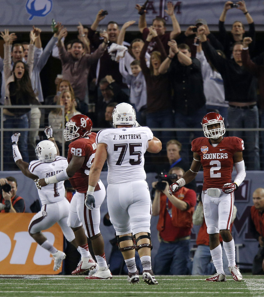 Photo - Oklahoma's Julian Wilson (2) walks away as Texas A&M 's Ben Malena (1) celebrates a touchdown during the Cotton Bowl college football game between the University of Oklahoma (OU)and Texas A&M University at Cowboys Stadium in Arlington, Texas, Friday, Jan. 4, 2013. Oklahoma lost 41-13. Photo by Bryan Terry, The Oklahoman