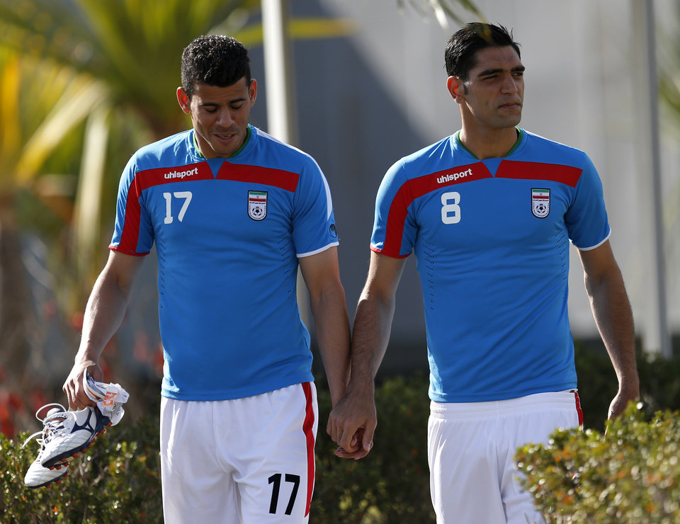 Photo - Iran's national soccer team players Mohammad Khanzadeh, left, and Sardar Azmoon hold hands while walking toward the pitch for warm ups before an international soccer friendly against Trinidad and Tobago at the Corinthians soccer team training center Sao Paulo, Brazil, on Sunday, June 8, 2014. Iran will play in group F of the 2014 soccer World Cup. (AP Photo/Julio Cortez)