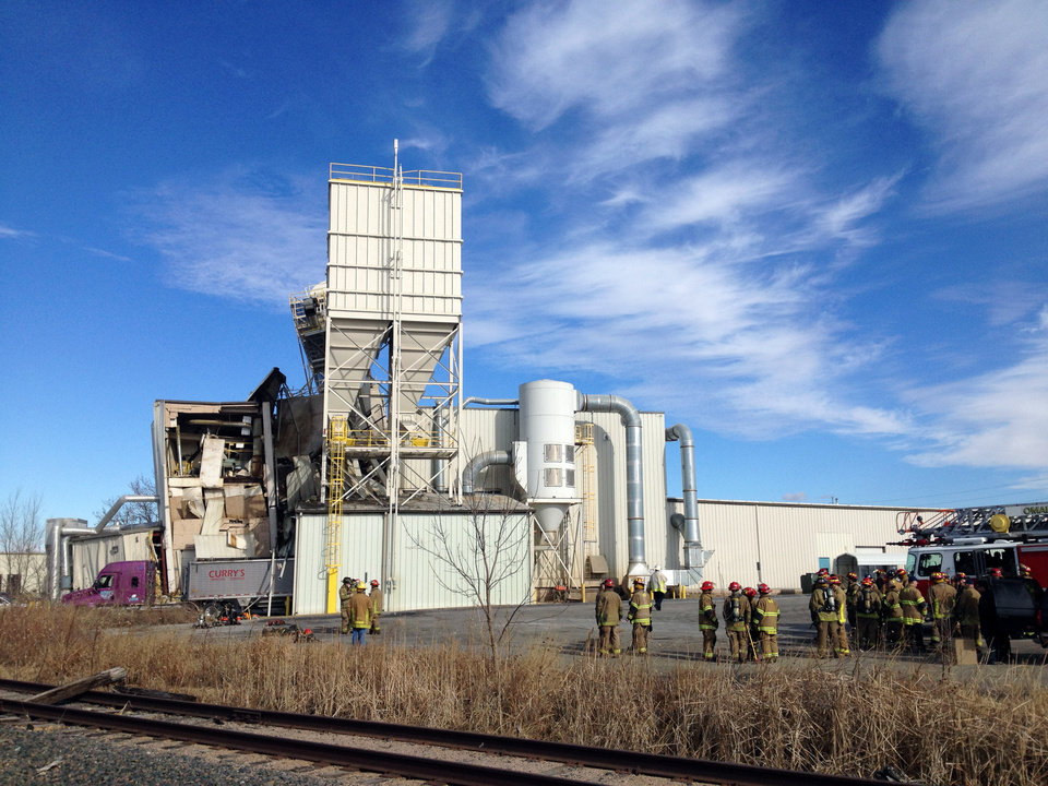 Photo - Firefighters stand outside the International Nutrition plant in Omaha, Neb., Monday, where a fire and explosion took place Jan. 20, 2014. At least nine people have been hospitalized and others could be trapped at the animal feed processing plant. (AP Photo/Nati Harnik)