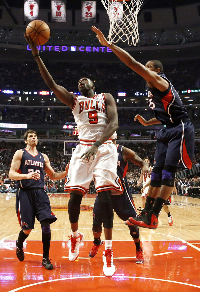 Chicago Bulls forward Luol Deng (9) shoots past Atlanta Hawks center Al Horford, right, during the first half of an NBA basketball game Monday, Jan. 14, 2013, in Chicago. (AP Photo/Charles Rex Arbogast)