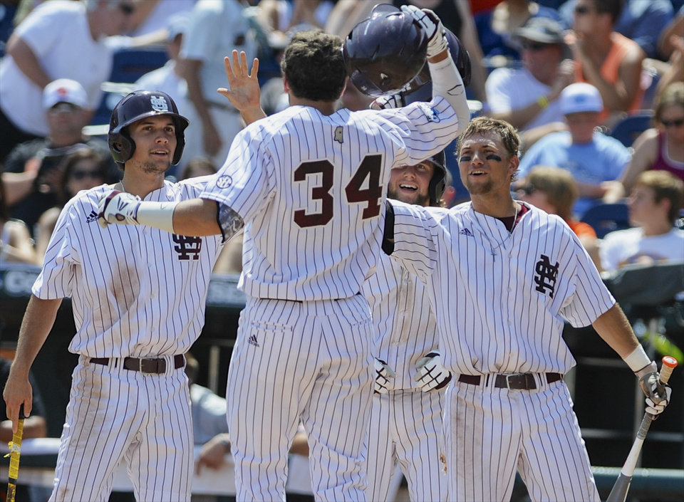 Photo - Mississippi State's Hunter Renfroe (34) is greeted by teammates, including Adam Frazier, left, after hitting a three-run home run against Oregon State in the fifth inning of an NCAA College World Series baseball game in Omaha, Neb., Friday, June 21, 2013. (AP Photo/Eric Francis)
