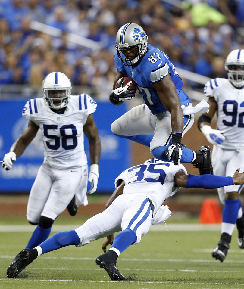 Photo - Detroit Lions tight end Brandon Pettigrew (87) leaps over Indianapolis Colts strong safety Joe Lefeged (35) during the second quarter of an NFL football game at Ford Field in Detroit, Sunday, Dec. 2, 2012. (AP Photo/Rick Osentoski)