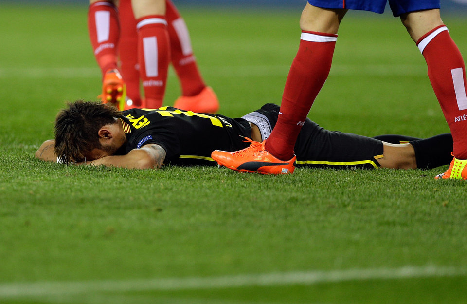 Photo - Barcelona's Neymar falls on the pitch during the Champions League quarterfinal second leg soccer match between Atletico Madrid and FC Barcelona in the Vicente Calderon stadium in Madrid, Spain, Wednesday, April 9, 2014. (AP Photo/Paul White)