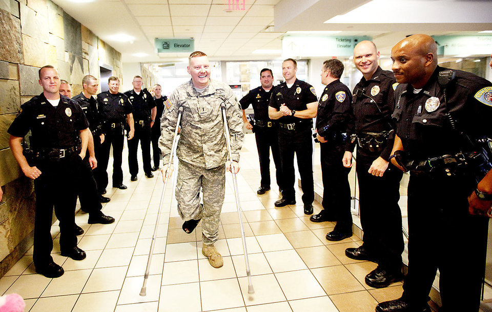 Photo - Right: Edmond police officer and Oklahoma National Guard soldier Kyle Stoy is greeted by fellow police officers as he arrives Thursday at Will Rogers World Airport in Oklahoma City.  Photo by Sarah Phipps, The Oklahoman