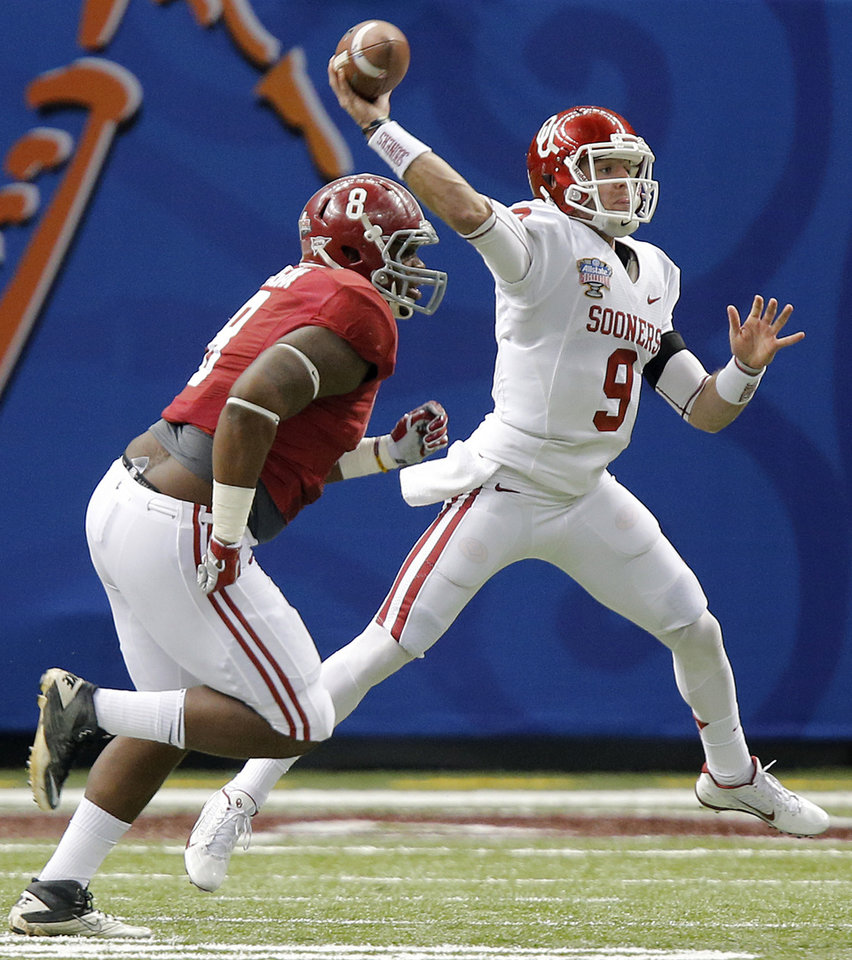 Photo - Oklahoma's Trevor Knight (9) passes the ball past Alabama's Jeoffrey Pagan (8) during the NCAA football BCS Sugar Bowl game between the University of Oklahoma Sooners (OU) and the University of Alabama Crimson Tide (UA) at the Superdome in New Orleans, La., Thursday, Jan. 2, 2014.  .Photo by Chris Landsberger, The Oklahoman