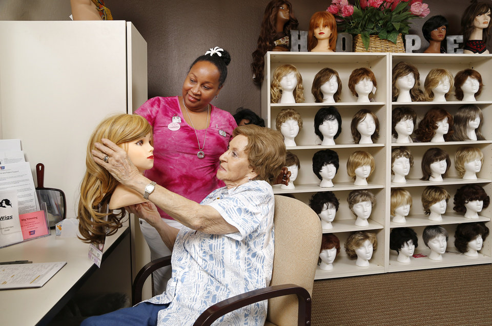 Photo -  Nicole Danley, left, looks at wig selections with Frieda Watts in the wig room at the American Cancer Society in Oklahoma City. [PHOTO BY JIM BECKEL, THE OKLAHOMAN]
