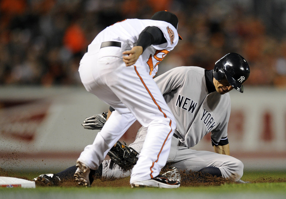 Photo -   Baltimore Orioles third baseman Manny Machado tags out New York Yankees Ichiro Suzuki, of Japan, as he tries to steal third base in the first inning of Game 1 of the American League division baseball series on Sunday, Oct. 7, 2012, in Baltimore. (AP Photo/Nick Wass)