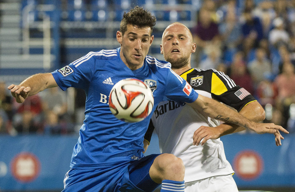 Photo - Montreal Impact's Ignacio Piatti, left, and Columbus Crew's Eric Gehrig battle for the ball during second half MLS soccer action in Montreal, Saturday, Aug. 30, 2014. (AP Photo/The Canadian Press, Graham Hughes)