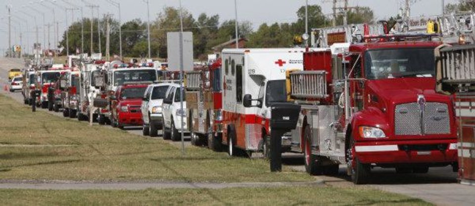 Photo - Fire and emergency vehicles line the road outside The Bridge Assembly of God in Mustang on Saturday during the funeral of Nichols Hills Fire Chief Keith Bryan.  PAUL HELLSTERN