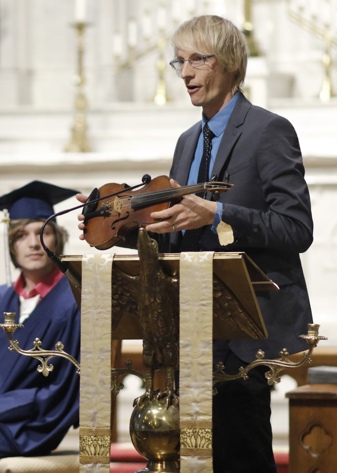 Photo - Kyle Dillingham plays his broken violin during the Teen Recovery Solutions (TRS) at Mission Academy high school graduation ceremony at St. Paul's Episcopal Cathedral, 127 NW 7th, in Oklahoma City, Thursday, May 26, 2016. Photo by Doug Hoke, The Oklahoman