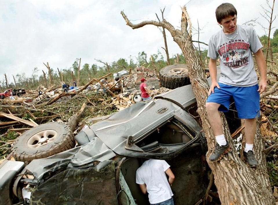 Standing on a fallen tree, Caden Bolles looks over damage to his family's home in Little Axe, Oklahoma on Tuesday, May 11, 2010. (AP Photo/The Oklahoman, John Clanton) ORG XMIT: OKOKL104