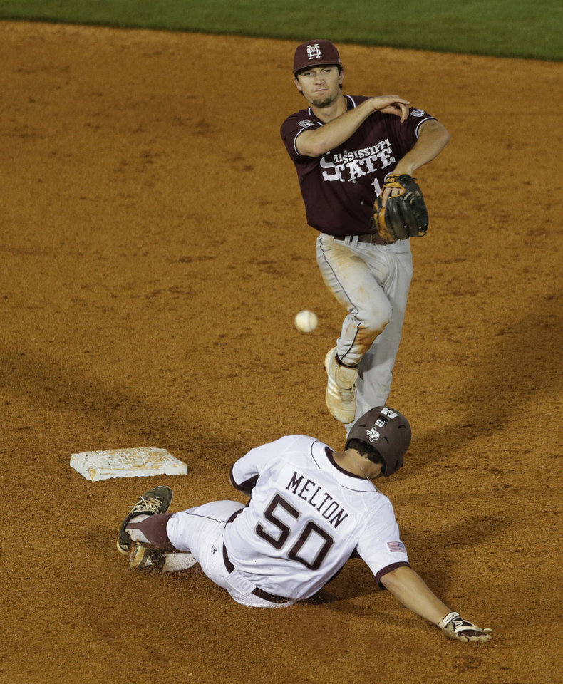 Photo - Mississippi State's Adam Frazier, top, turns a double play as Texas A&M's Hunter Melton slides into second in the fourth inning of their Southeastern Conference Tournament college baseball game at the Hoover Met in Hoover, Ala., Thursday, May 23, 2013. (AP Photo/Dave Martin)