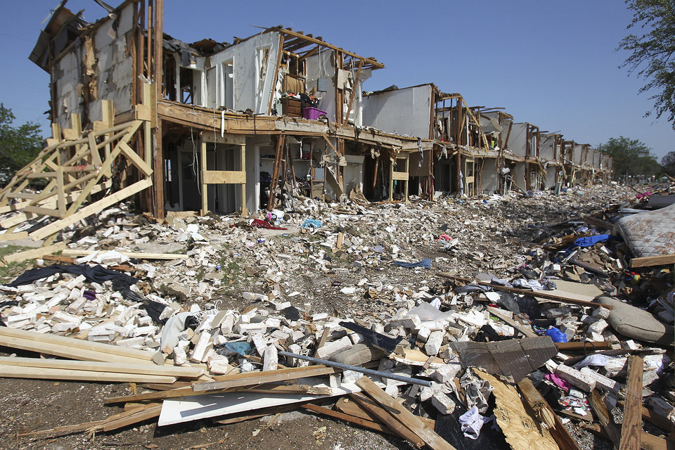 Debris litters the ground outside a destroyed apartment complex adjacent to the site of the fire and explosion in West, Texas on Wednesday, April 24, 2013. The explosion at West Fertilizer which killed 14 people left a crater more than 90 feet (27 meters) wide and blasted the walls and windows off dozens of buildings in the town of 2,700. (AP Photo/The San Antonio Express-News, Tom Reel, Pool)