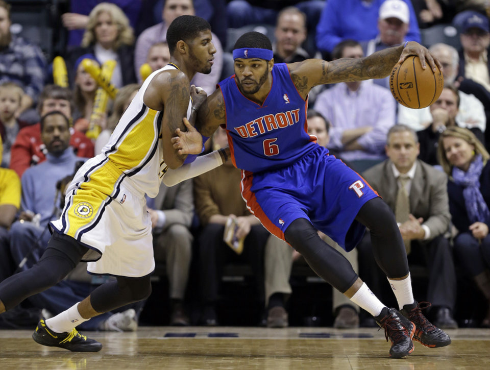Photo - Indiana Pacers forward Paul George, left, defends Detroit Pistons forward Josh Smith in the second half of an NBA basketball game in Indianapolis, Monday, Dec. 16, 2013. The Pistons defeated the Pacers 101-96. (AP Photo/Michael Conroy)