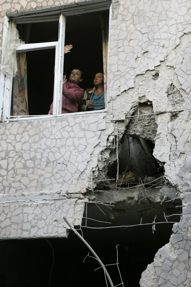 Photo - Women try to open a window in their damaged house after shelling in the city of Slovyansk, Donetsk Region, eastern Ukraine Monday, June 30, 2014. Residential areas came under shelling on Monday morning from government forces. (AP Photo/Dmitry Lovetsky)