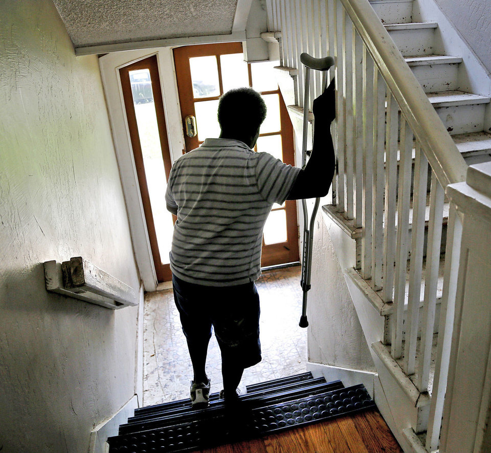 Photo - Hardiman navigates the stairs of his apartment. He uses a crutch because he was attacked and left for dead in an Oklahoma City park 17 years ago. He suffered a stroke that paralyzed his left side after that 1996 beating.  Jim Beckel - Photo by Jim Beckel, The Oklahom