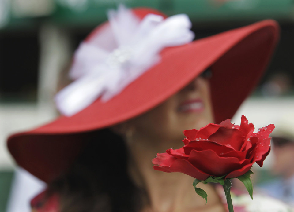 Photo - Mary Bowe, from Maples, Fla., holds a rose while sitting in the grandstand before the 138th Kentucky Derby horse race at Churchill Downs, Saturday, May 5, 2012, in Louisville, Ky. The Run for the Roses draws them to Churchill Downs. But what race goers wear is as much a spectacle in itself. (AP Photo/Michael Conroy) ORG XMIT: NY229