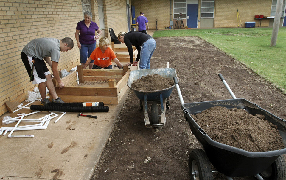 Photo - Workers place netting inside a planter. Volunteers are planting a garden at Stanley Hupfeld Academy at Western Village. Photo by Jim Beckel, The Oklahoman.  Jim Beckel