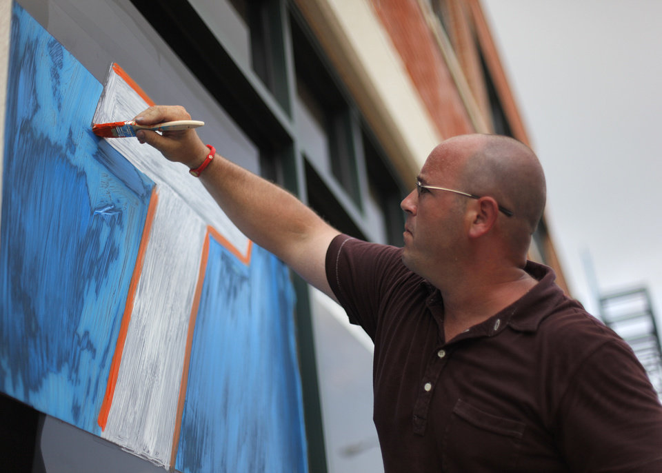 Photo - OKLAHOMA CITY THUNDER / NBA FINALS / NBA BASKETBALL / SUPPORT / MIAMI HEAT:  Daniel Cochran, an employee at The Brace Place, paints the windows outside of his office building in Oklahoma City, Monday, June 11, 2012.  Photo by Garett Fisbeck, The Oklahoman