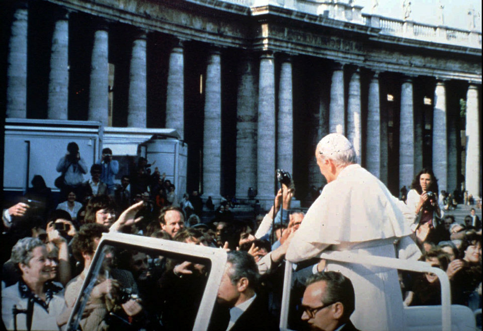 Photo - In this May 13, 1981 file photo provided by Vatican paper L'Osservatore Romano, Mehmet Ali Agca, left, holds a Browning HP 9mm handgun to shoot Pope Jonh Paul II at the Vatican. Alitalia Flight 488 landed in Krakow, Poland on Tuesday, March 18, 2014 with some very special cargo on board: The gun used to shoot Pope John Paul II. Monsignor Dariusz Ras, the Polish priest who runs the John Paul II museum in the late pope's childhood home in Wadowice, transported the pistol from Rome to Poland for the museum's upcoming exhibit in honor of John Paul's April 27 canonization, Alitalia said. Mehmet Ali Agca used the Browning HP 9mm handgun to shoot John Paul in the abdomen in St. Peter's Square on May 13, 1981. The pope spent nearly three weeks in the hospital recovering. (AP Photo/L'Osservatore Romano)
