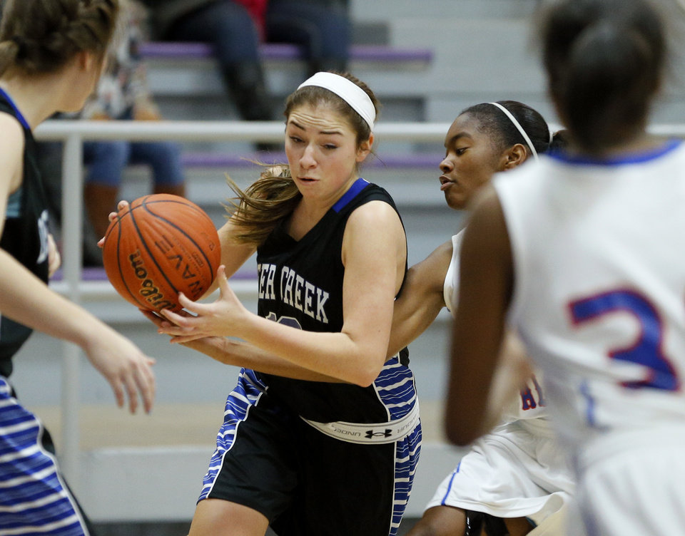 Photo - Deer Creek's Whitney Jones, left, goes past Millwood's Deztinee Gooden during their high school basketball game in the Bethany Classic tournament in Bethany, Okla., Friday, Jan. 10, 2014. Photo by Bryan Terry, The Oklahoman