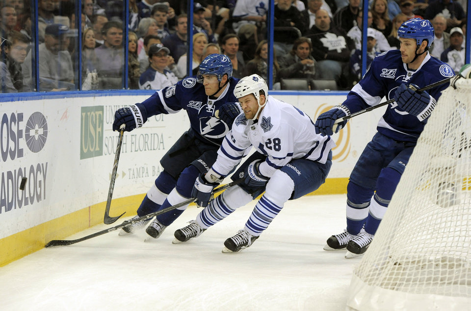 Photo - Toronto Maple Leafs right wing Colton Orr, center, defends the puck against Tampa Bay Lightning defenseman Matt Carle, left, and Lightning defenseman Eric Brewer during the first period of an NHL hockey game Tuesday, Feb. 19, 2013, in Tampa, Fla. (AP Photo/Brian Blanco)