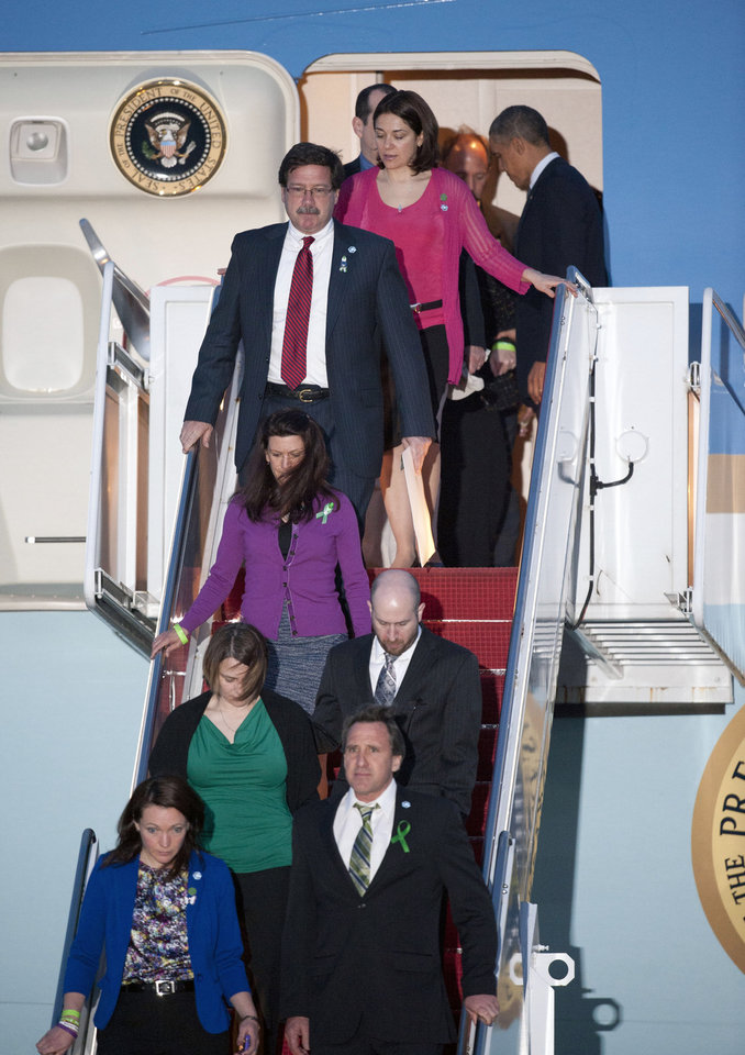 Photo - President Barack Obama stands in the door of Air Force One, top right,  at Andrews Air Force Base, Md., Monday, April 8, 2013 with families who lost relatives in the Sandy Hook Elementary School shooting. Obama was returning from Hartford, Conn., where he spoke at the University of Hartford, near the state capitol where last week the governor signed into law some of the nation's strictest gun control laws. (AP Photo/Cliff Owen)