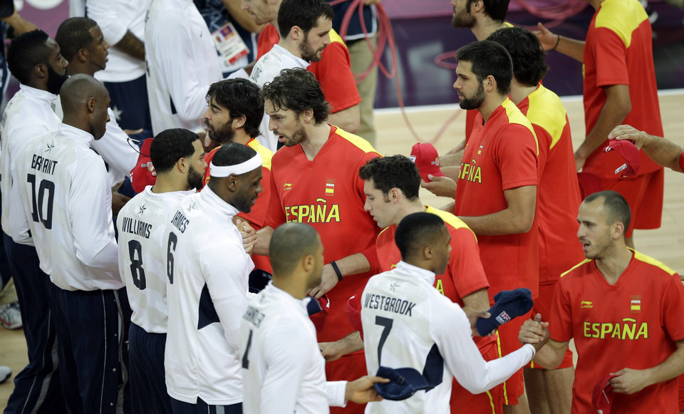 Basketball players for the United States and Spain shake hand before the start of the men's gold medal basketball game at the 2012 Summer Olympics, Sunday, Aug. 12, 2012, in London. (AP Photo/Matt Slocum)