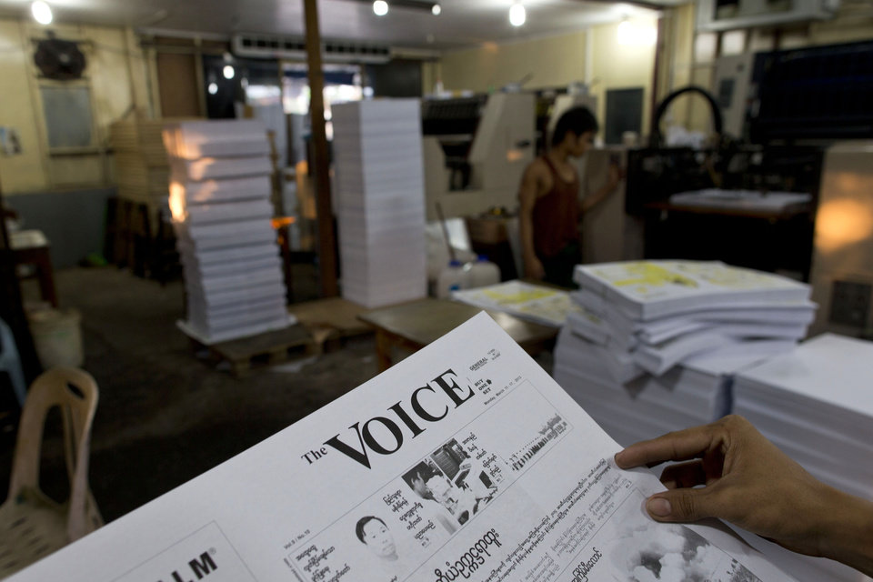 "In this March 15, 2013 photo, a printing worker of weekly journal ""The Voice,"" inspects proof page in a printing press in Yangon, Myanmar. The Voice Weekly news journal was temporarily suspended for 6-times during the period of 2005-2012. After eight months and 26 hearings, Myanmar's ministry of mining dropped its controversial defamation lawsuit against the journal in early 2013. The lawsuit originated from publication of corruption allegations against the ministry in 2012.  Myanmar's newly energized press corps is calling on the government to revise a proposed new publishing law, saying it will mark a severe setback to press freedoms and replace the country's old censorship regime with other forms of repression. (AP Photo/Gemunu Amarasinghe)"